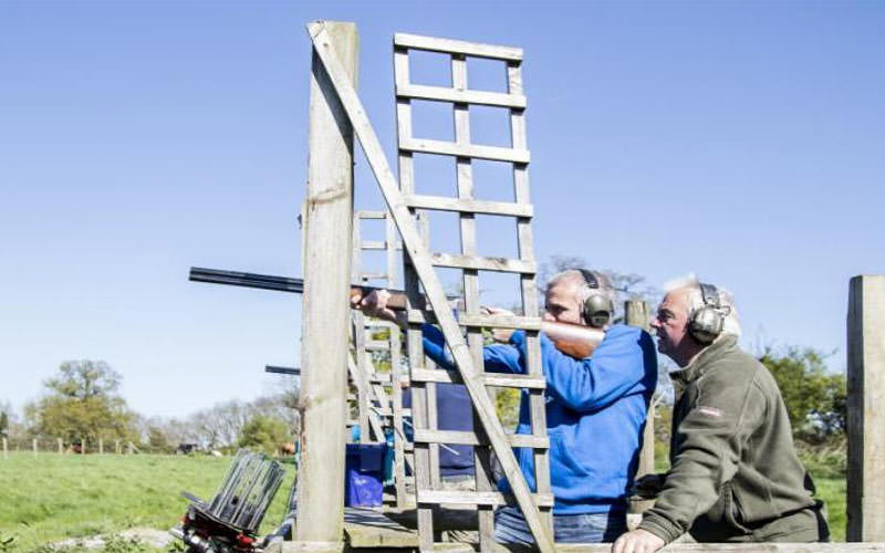 Two men shooting a shotgun, clay pigeon shoot.