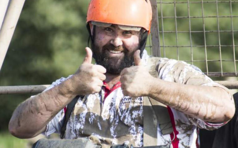 Cute bearded man giving a double thumbs up while wearing an orange helmet, covered in mud