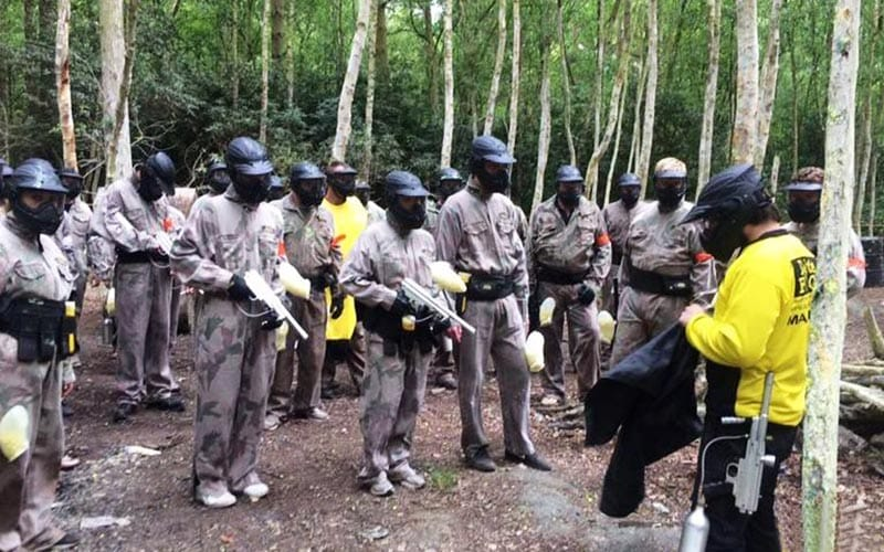 People wearing camouflage overalls and black helmets, all holding their paintball guns