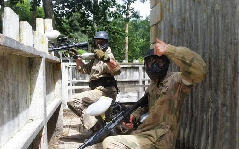 Two people with their thumbs up, while paintballing
