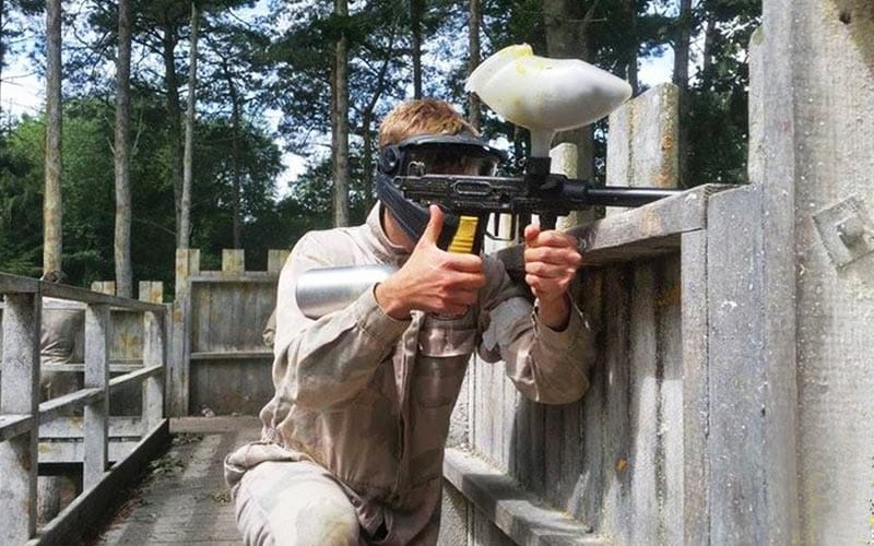 A man holding a paintball gun over a wooden fence at his enemy