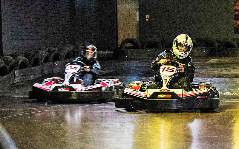 Two people racing in go karts on an indoor track