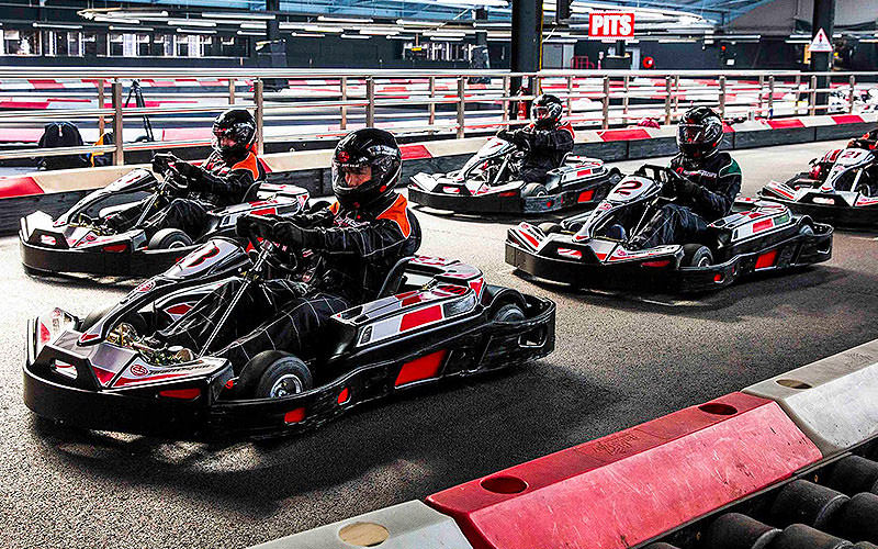 Five people lined up in go karts, ready to start a race