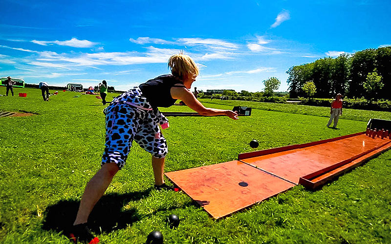 A woman playing boules outside