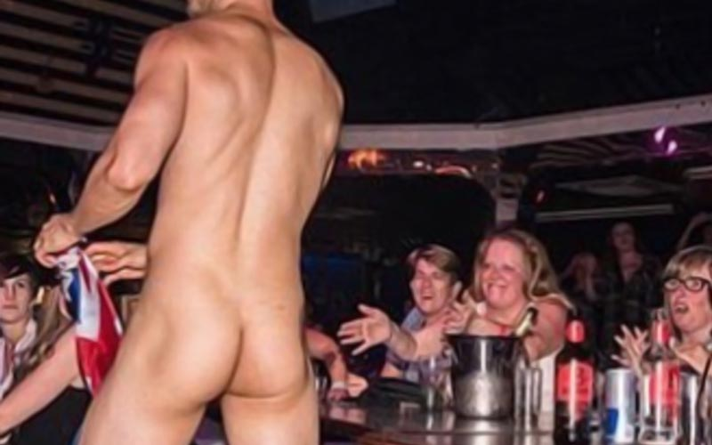 A naked stripper in front of lots of women