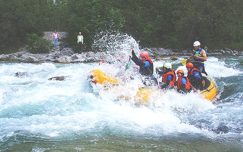 People battling white water rapins in a dinghy on the river