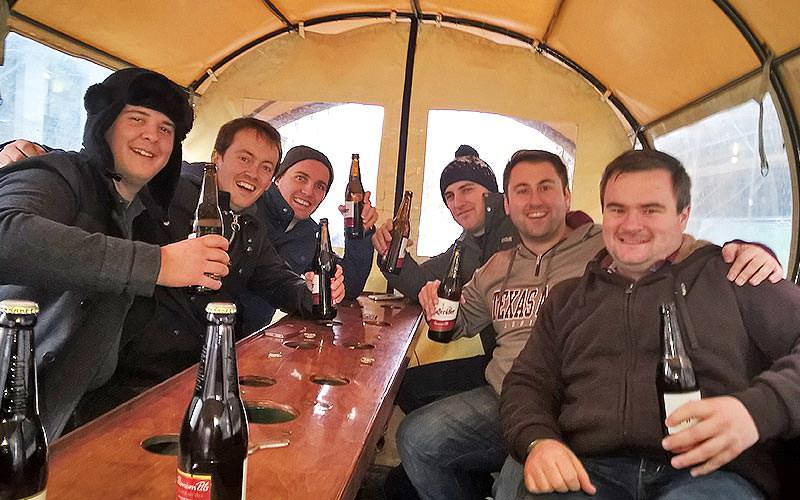Group of men sat at a table inside a beer coach and drinking bottles of beer