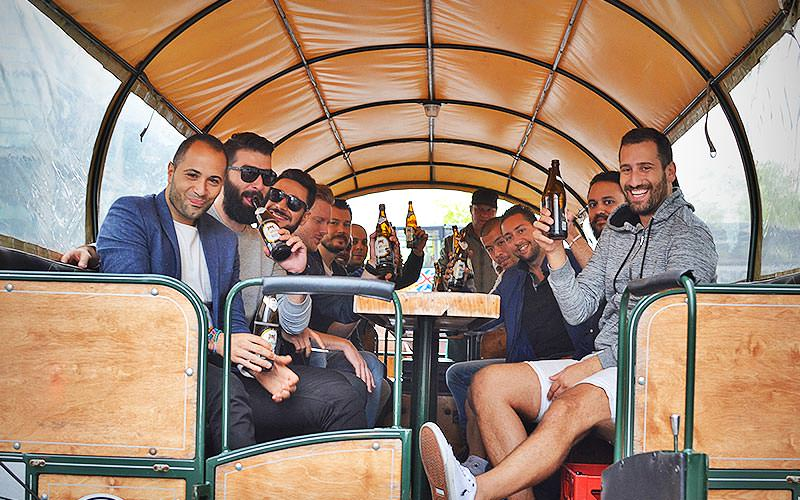 Group of men sat at a table inside a beer coach, posing for a picture and drinking bottles of beer
