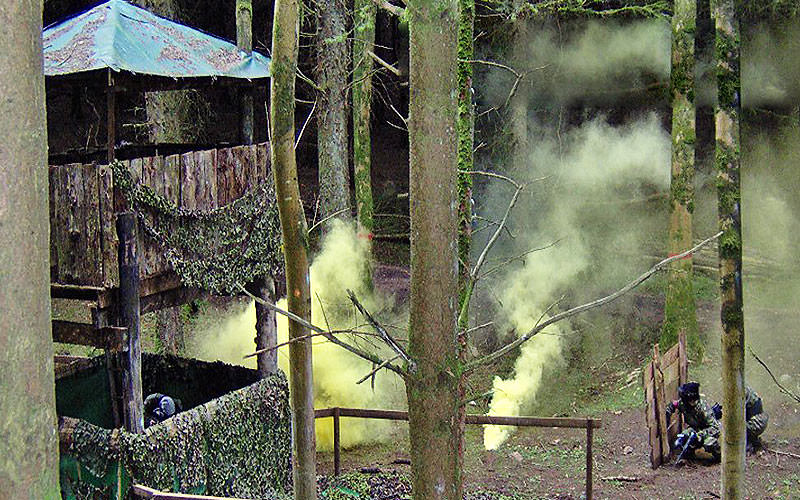 Outdoor watch tower with two people hiding behind a fence and playing paintball