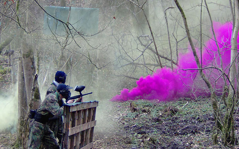 Two men standing behind a fence in camouflage gear, with pink smoke in the foreground