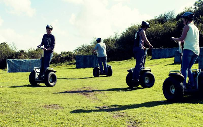 Four people driving segways around a green field