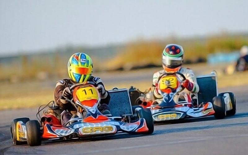 Two people in go karts, on a track outside