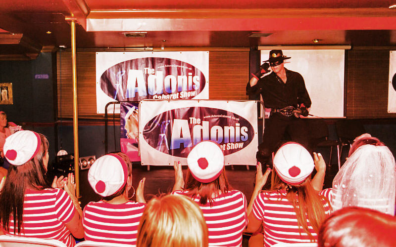 A man in a Zorro costume performing to women in the crowd in Where's Wally outfits