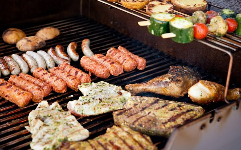 Sausages, burgers, steaks, chicken and kebabs on a barbecue