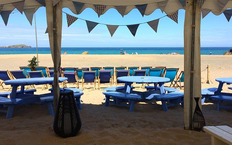 A marquee with bunting and blue tables and chairs on a beach during the day