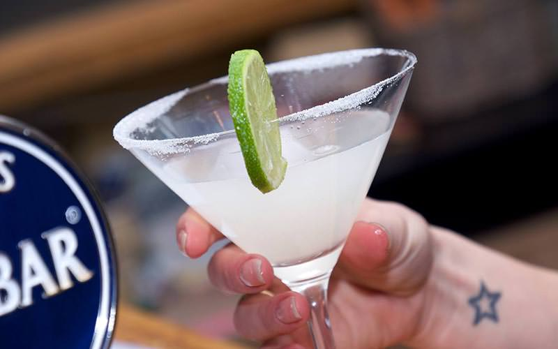 A cocktail with sugar on the rim and a lime on the side