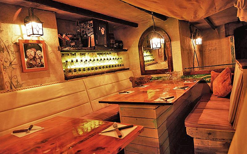 Two wooden booths set for dinner, with pictures and lamps along the wall