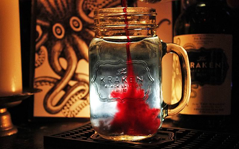 A glass jar of clear liquid with a red shot inside