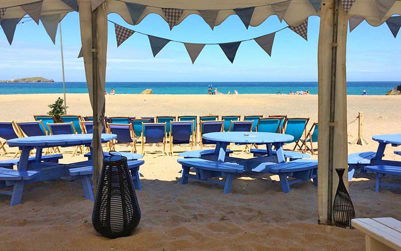 A gorgeous sitting area on the beach, with bunting in the background