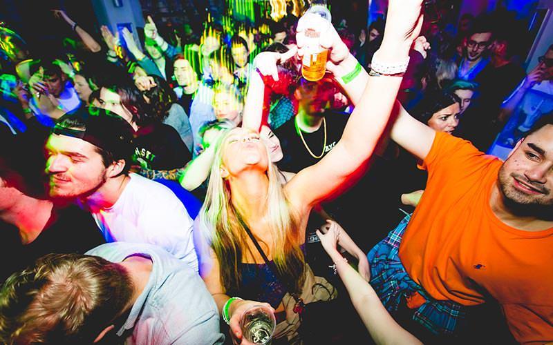Men and women dancing on a dance floor to green lights