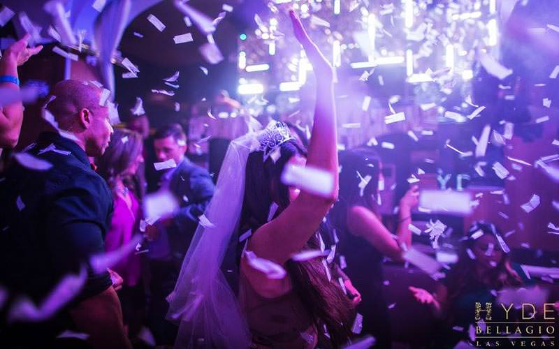 A woman dancing under falling white confetti and wearing a costume wedding veil