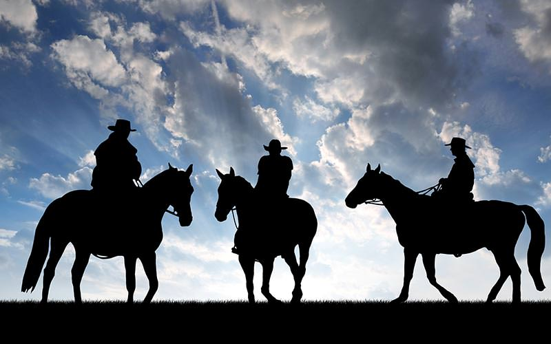 The silhouettes of three men riding horses under a cloudy sky