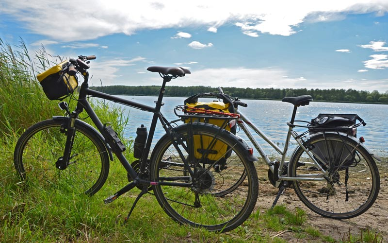 Two bikes on grass with a river in the backgroud