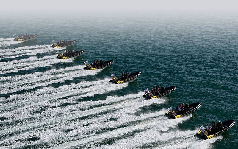 Eight RIB boats going out to sea, leaving white foamy trails behind them