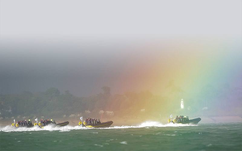 Some RIB boats surfing beneath a rainbow