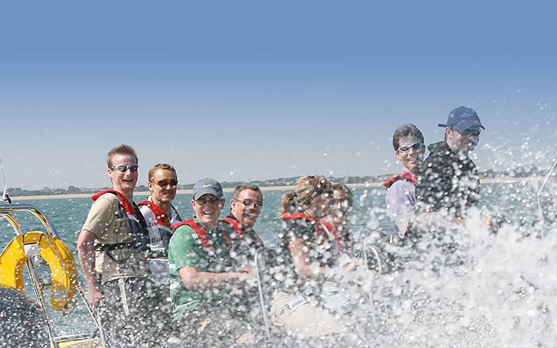 People on a RIB boat with the splash from the sea coming up into the camera