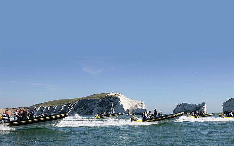 Some people travelling on RIB boats to a backdrop of white cliffs