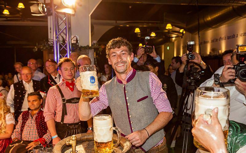 A man holding up a stein, with people looking on in the background