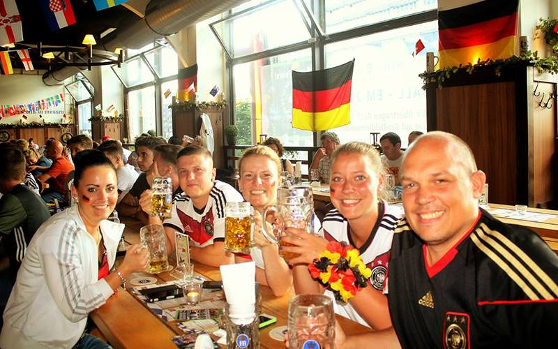 Men and women toasting with steins at a table