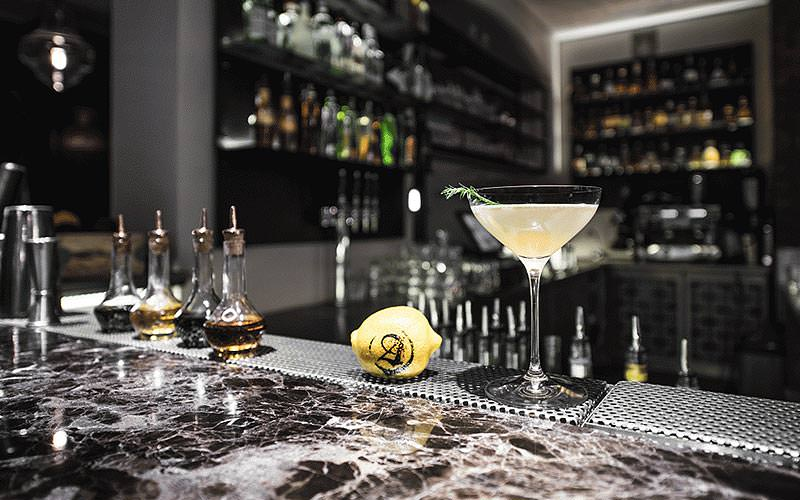 A cocktail on a marble bar top, with a bar in the background