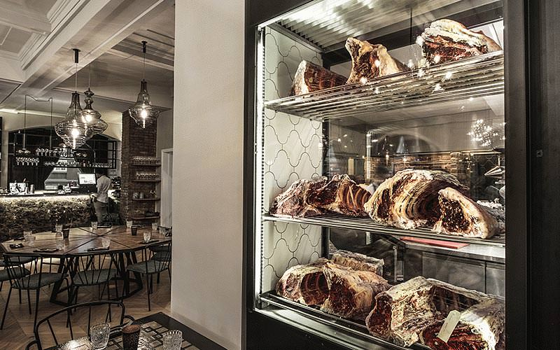 Meat on a glass shelf with a table in the background
