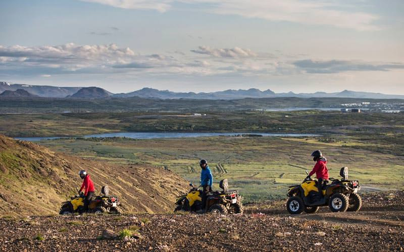 Three people quad biking to a backdrop of mountains