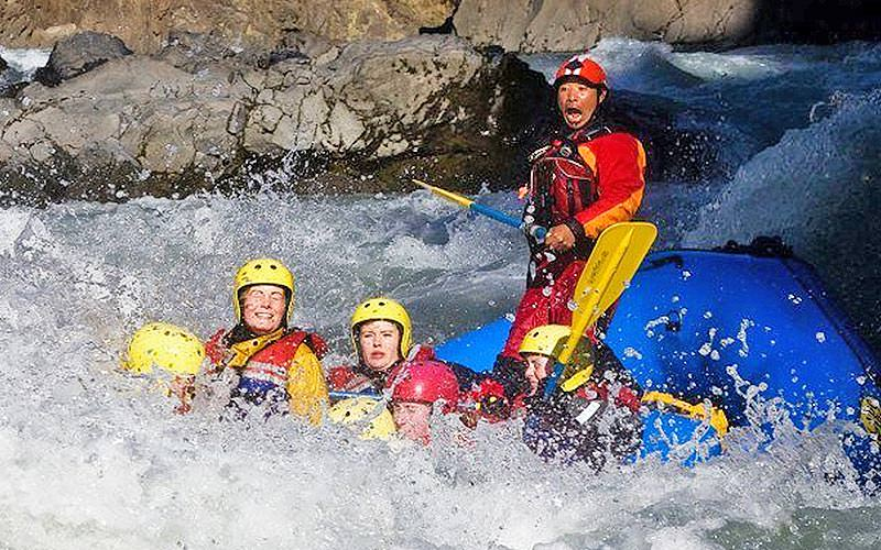 Four people white water rafting in a river