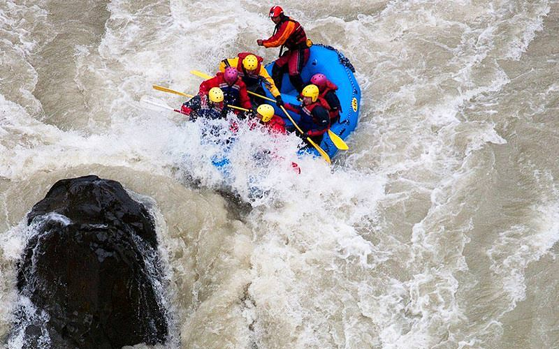 Bird's eye view of four people white water rafting in a river