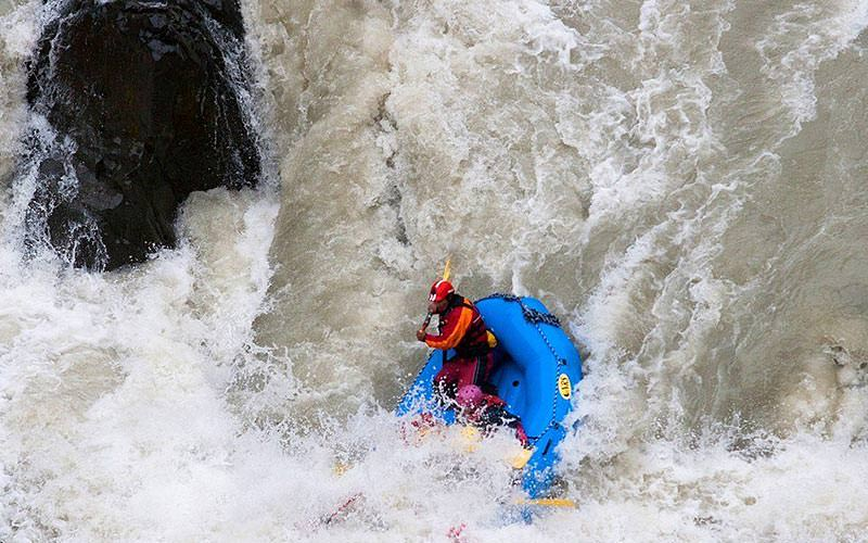 Bird's eye view of people white water rafting in a river