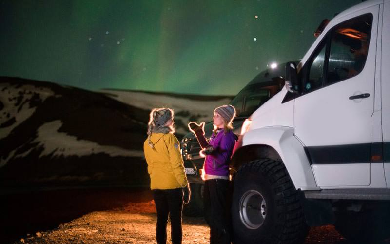 Two people beside a white truck with the Northern Lights in the background