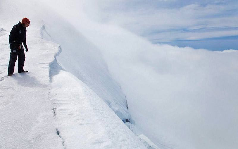 A man looking over the edge of a glacier
