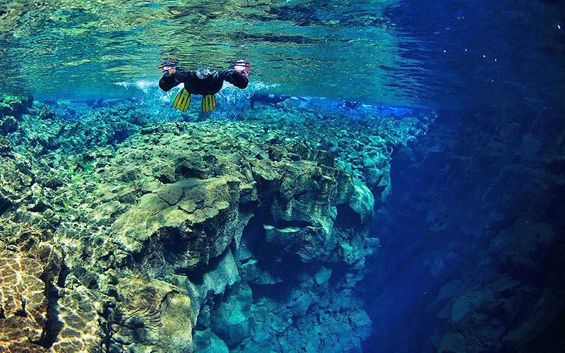 A man snorkelling with rock formations underwater