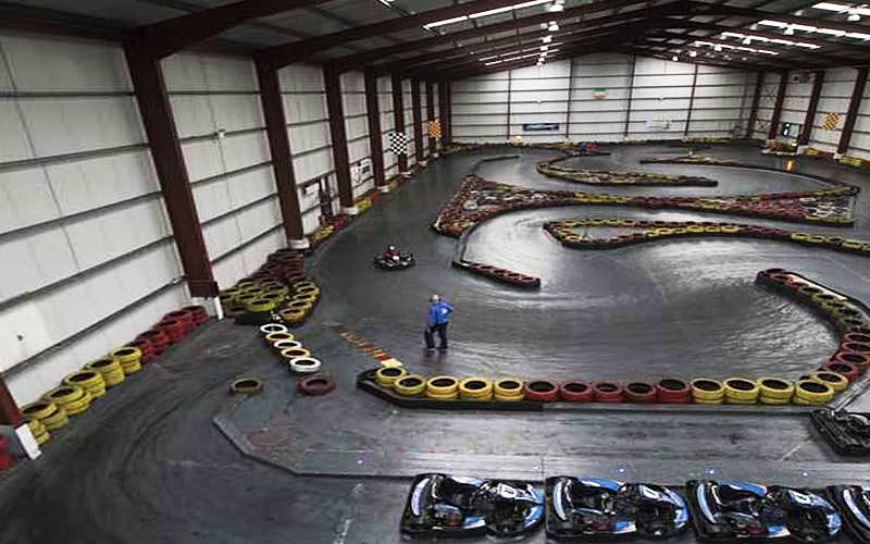 A view over an indoor go karting track with yellow and red tyres marking the track