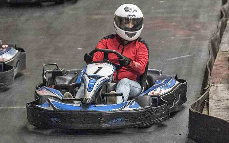 A person driving a blue go kart on an indoor circuit