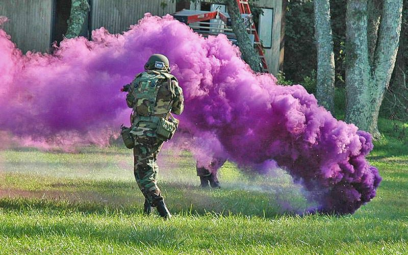 A man wearing camouflage and a helmet running past a plume of purple smoke