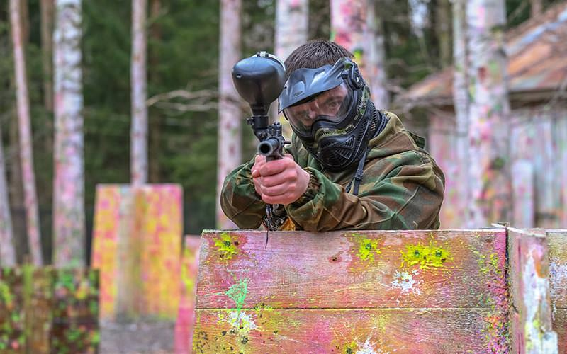 A man wearing camouflage overalls and a mask standing behind a wooden board and aiming a paintball marker