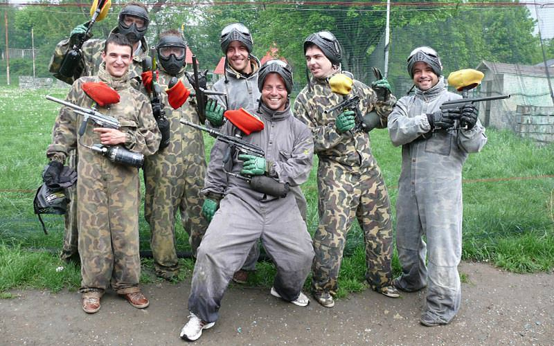A group of people wearing overalls and masks, holding paintball markers and posing
