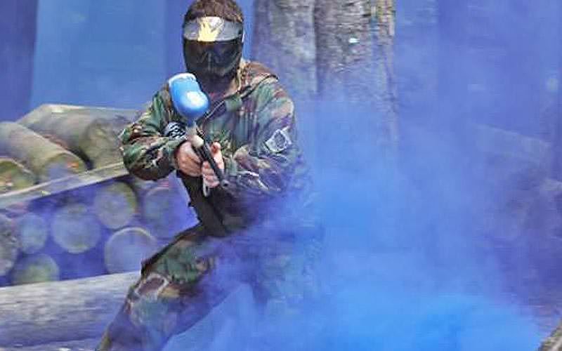A man wearing camouflage overalls and a mask, holding a paintball marker and surrounded by blue smoke
