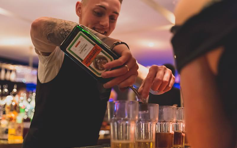 A bartender pouring out Jager into cups
