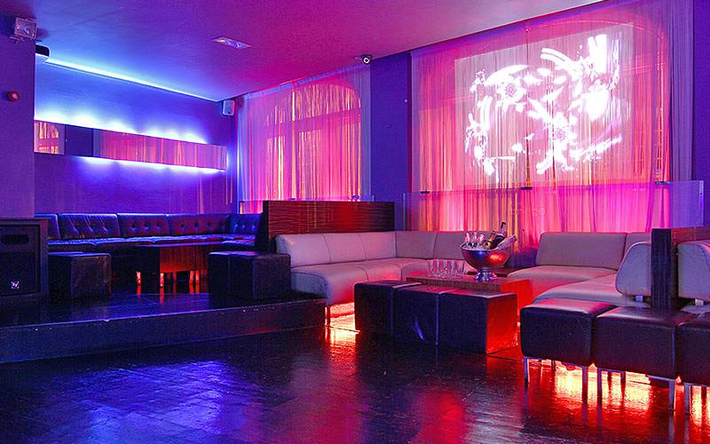 Empty, white leather booths along a wall in a club, to a backdrop of pink and blue lights
